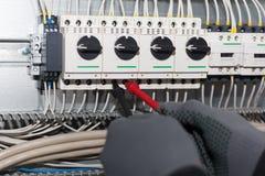 L'elettricista dell'ingegnere sta collaudando una macchina elettrica fotografia stock