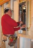 L'elettricista fa i collegamenti in casella del comitato Fotografia Stock Libera da Diritti
