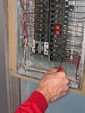 L'elettricista fa i collegamenti in casella del comitato Fotografia Stock