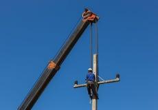 L'elettricista installa il cavo sul palo di energia elettrica con la gru Fotografia Stock