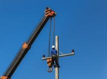 L'elettricista installa il cavo sul palo di energia elettrica con la gru Fotografie Stock Libere da Diritti