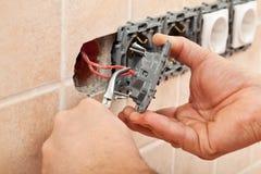 L'elettricista passa l'installazione dei cavi in un dispositivo della parete Fotografie Stock