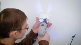 L'elettricista sta installando un doppio incavo su una parete bianca, fissantesi facendo uso di un cacciavite senza cordone in un video d archivio