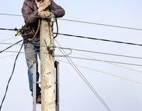 L'elettricista sul palo lavora con i cavi Fotografia Stock Libera da Diritti