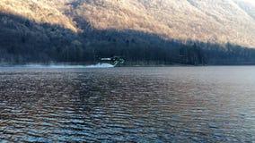 L'elicottero dei pompieri prende l'acqua nel lago in un fuoco della montagna sopra il lago Ghirla, provincia di Varese, Italia stock footage