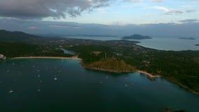 L'elicottero sorvola gli yacht attraccati in una baia vicino al vecchio paesino di pescatori a Phuket Fotografia Stock