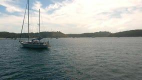 L'elicottero sorvola l'yacht attraccato in una roccia vicina della baia Fotografie Stock