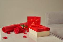 L'emballage cadeau de Valentine avec les rouleaux de papier et le bouquet de a monté Photos stock