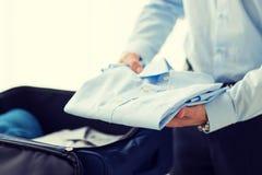 L'emballage d'homme d'affaires vêtx dans le sac de voyage Photo stock