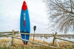 L'emballage tiennent le paddleboard et la palette Photographie stock