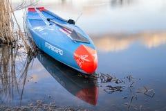 L'emballage tiennent le paddleboard sur un lac calme Image libre de droits