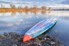 L'emballage tiennent le paddleboard sur un lac calme Photo stock