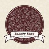 L'emblema del negozio del forno con i dolci disegnati a mano e cuoce Fotografia Stock