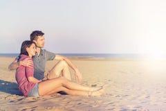 L'embrassement de couples admire le coucher du soleil dans l'océan Photos stock