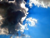 L'emergenza del sole dalle nuvole nel cielo Fotografie Stock
