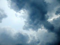 L'emergenza del sole dalle nuvole nel cielo Fotografia Stock