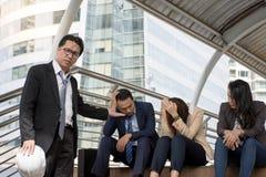 L'employé a été grondé par le surveillant que le sentiment soit participation sérieuse sa tête tandis que son patron se plaint image stock