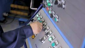 L'employé actionne le panneau industriel avec des boutons de contrôle à un ensemble industriel banque de vidéos