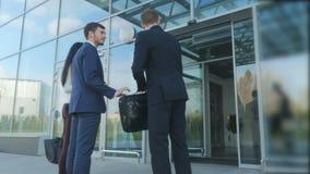 L'employé d'aéroport salue les couples entrant dans le bâtiment d'aéroport banque de vidéos