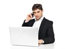 L'employé de bureau avec l'ordinateur portable parle par le téléphone portable Photos stock