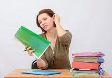 L'employé de bureau de fille pensivement tient des documents dans un dossier et enlève des cheveux Image libre de droits