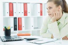 L'employé de bureau féminin ennuyé s'assied à son bureau et examine la distance Images libres de droits