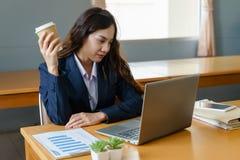 L'employé de bureau féminin porte les travaux bleu-foncé de costume avec l'ordinateur portable tout en buvant du café dans le vis images stock