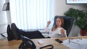 L'employé de bureau prenant une pause-café avec ses pieds nus a augmenté sur le bureau et une tasse d'expresso dans des ses mains Photographie stock