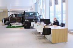 L'employé de concessionnaire automobile et deux voitures Images libres de droits
