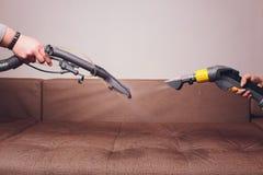 L'employé de deux nettoyeurs à sec avec l'extracteur de poussière universel dans l'appartement photos stock