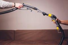 L'employé de deux nettoyeurs à sec avec l'extracteur de poussière universel dans l'appartement image libre de droits