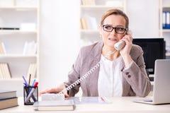 L'employé de femme d'affaires parlant au téléphone de bureau Images stock