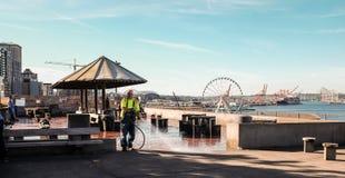 L'employé de la ville arrose vers le bas la plaza au jet au bord de mer de Seattle Photos libres de droits