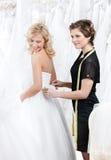 L'employé de magasin aide à la jeune mariée à mettre la robe dessus Image stock