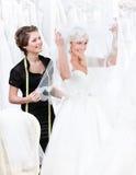 L'employé de magasin aide à la mariée à mettre le weddi Images stock