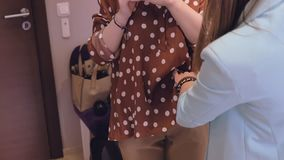 L'employé de magasin de femme aide la dame à essayer sur le chemisier brun de point de polka et les pantalons beiges dans le mouv clips vidéos