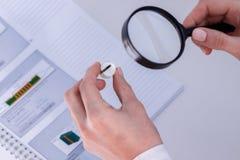 L'employé du département du contrôle technique vérifie des transitions de solderability dans le conseil Photo stock