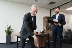 L'employé est venu chez le directeur avec un rapport Le directeur joue au golf dans le bureau Image stock