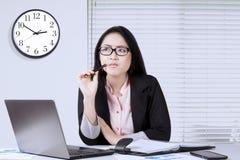 L'employé féminin pense l'idée dans le bureau Photo libre de droits