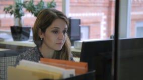 L'employé féminin regarde l'écran d'ordinateur tout en se reposant au bureau dans le bureau banque de vidéos