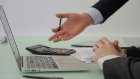 L'employé masculin effectue des calculs utilisant la calculatrice à la principale société banque de vidéos