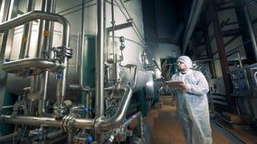L'employé masculin inspecte des barils de brassage dans des lieux d'usine clips vidéos
