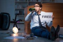 L'employé mis le feu pendant la crise buvant dans l'effort et le désespoir photos stock