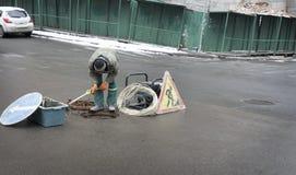 L'employé a ouvert la trappe dans la rue pour éliminer la situation d'urgence Image libre de droits