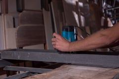 L'employé traite la coquille de noix La table moderne Compteur de barre Un charpentier petit atelier affaires dans le garage photos libres de droits