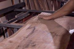 L'employé traite la coquille de noix La table moderne Compteur de barre Un charpentier petit atelier affaires dans le garage image libre de droits