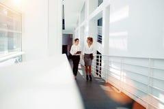 L'employée tenant le pavé tactile et parlent des idées à l'associé tout en marchant dans l'intérieur de hall de bureau, images stock