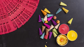L'encens coloré et les bougies lumineuses sur la main rouge évente sur le verrat de craie Photo libre de droits