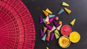 L'encens et les bougies colorés sur la main rouge évente sur le backg de panneau de craie Images libres de droits