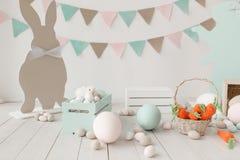 L'encore-vie de Pâques avec les oeufs, la silhouette de papier de lapin de carottes et la guirlande sur le mur Copiez le fond de  Photographie stock libre de droits